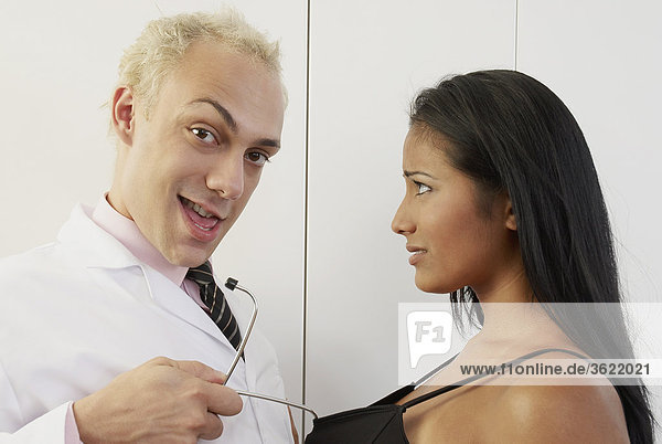 Portrait of a male doctor pulling a young woman with a stethoscope