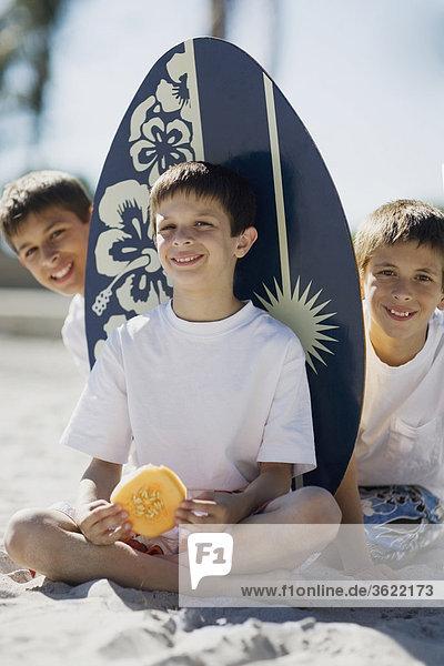 Portrait von zwei jungen und ein Teenager am Strand sitzen und lächelnd
