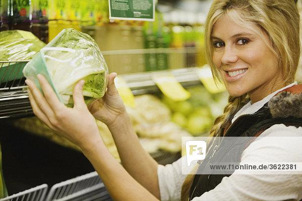 Portrait einer jungen Frau mit einem Kohlkopf in einem Supermarkt