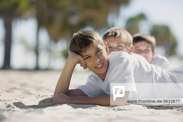 Zwei jungen und ein Teenager liegen am Strand