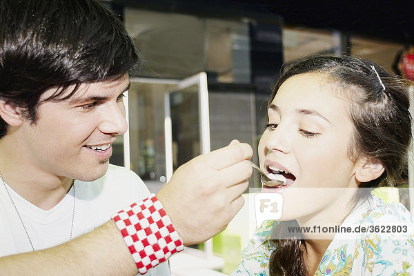 Close-up of a young man feeding ice-cream to a young woman
