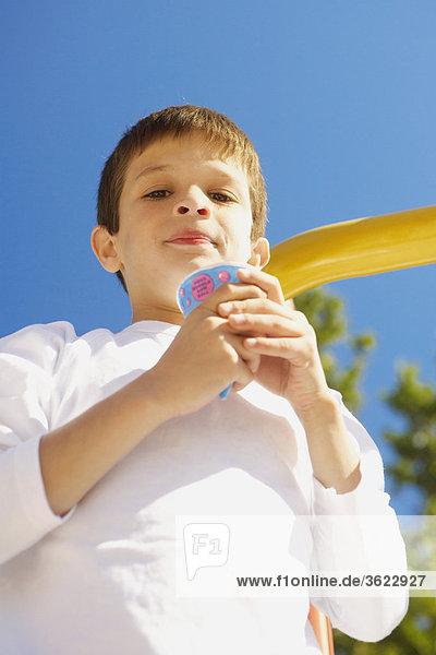 Untersicht of a Junge hält ein Eis und Grinsen