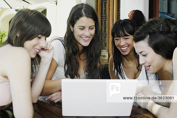 Zwei Frauen und zwei junge Frauen mit einem Laptop lächelnd Mitte