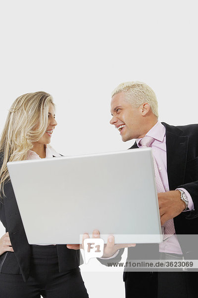 Low angle view of a businesswoman and a businessman using a laptop