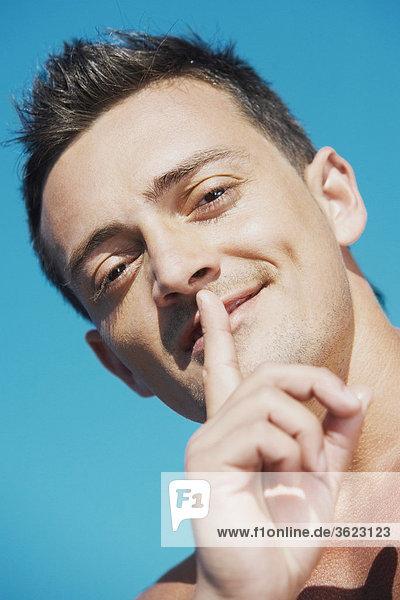 Porträt eines jungen Mannes mit dem Finger auf den Lippen