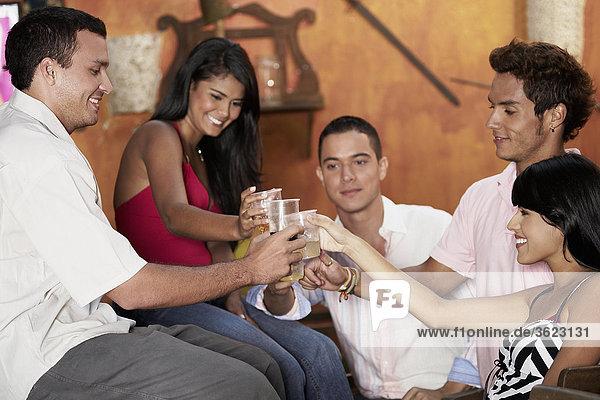 Nahaufnahme der zwei junge Frauen und drei junge Männer Toasten Gläser cocktail