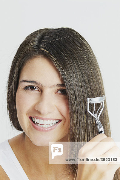 Portrait of a young woman crimping her hair