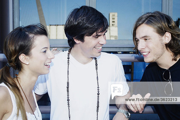 Close-up of a young couple and a teenage boy smiling