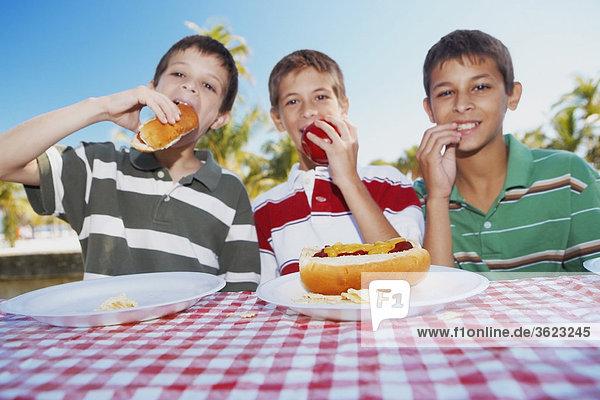 Hot Dog Hot Dogs sitzend Portrait Jugendlicher Junge - Person 2 Apfel essen essend isst Tisch