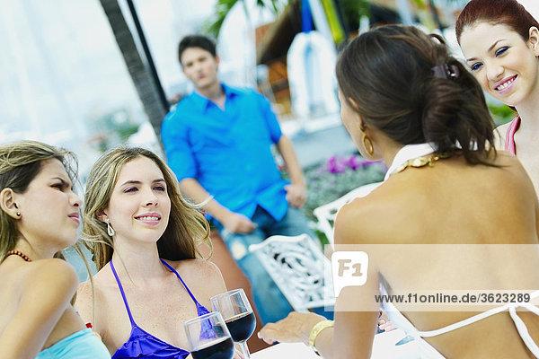 Vier junge Frauen sitzen in einem Restaurant mit einem jungen Mann im Hintergrund