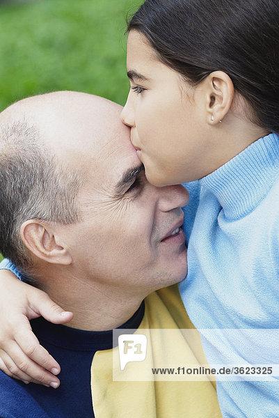 Nahaufnahme von einem Mädchen küssen ihres Vaters auf der Stirn