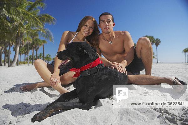 Portrait von Mitte Erwachsenen Mann und eine junge Frau mit ihrem Hund am Strand sitzen
