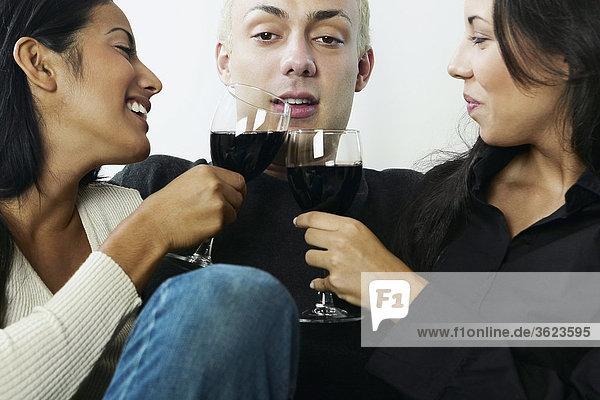 Nahaufnahme eines jungen Mannes mit zwei junge Frauen halten Gläser Wein sitzen