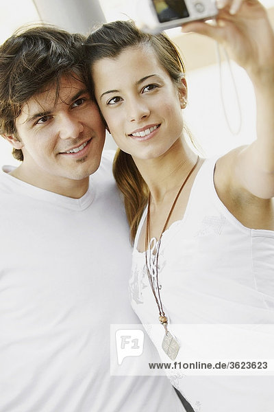 Close-up of a young couple taking a photograph of themselves