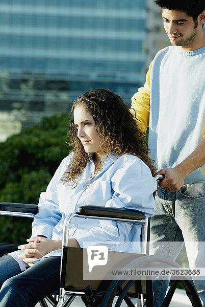 Junger Mann drängen Rollstuhl mit einer jungen Frau