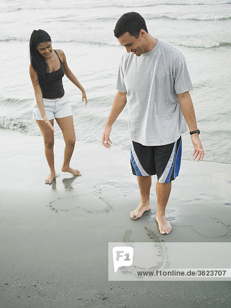 Young couple standing on the beach and looking down