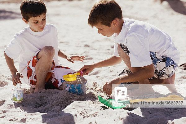 Zwei Jungs spielen mit Sand Eimer und Schaufel am Strand