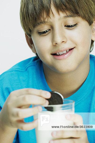 Nahaufnahme eines jungen Eintauchen Cookies in einem Glas Milch