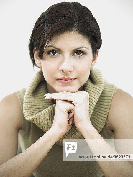 Portrait einer jungen Frau mit der Hand auf dem Kinn