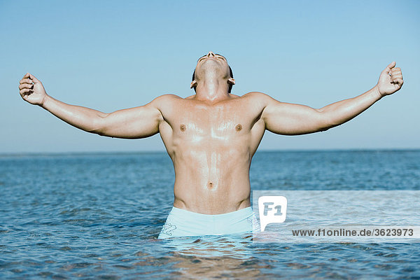 stehend Wasser Mann jung Arme ausbreiten Arme ausstrecken strecken