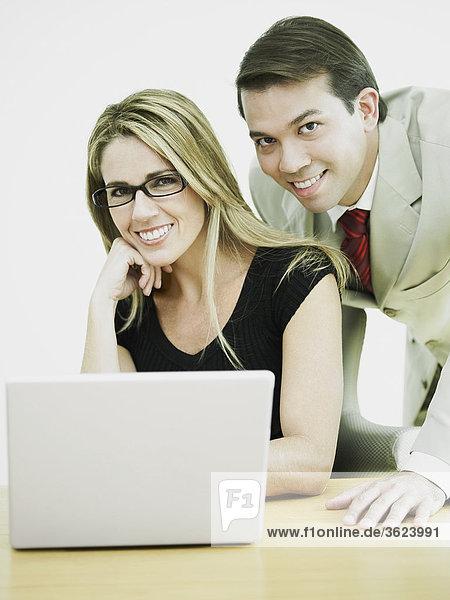 Portrait eines Kaufmanns und einer geschäftsfrau an einen laptop