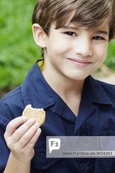 Bildnis eines Knaben hält einen Cookie und lächelnd