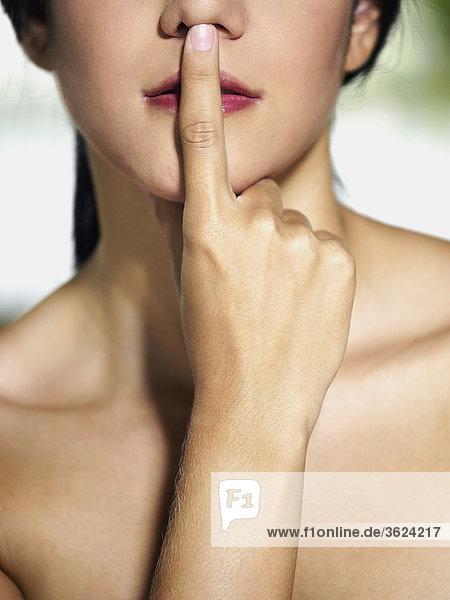 Nahaufnahme einer jungen Frau mit Finger auf ihre Lippen