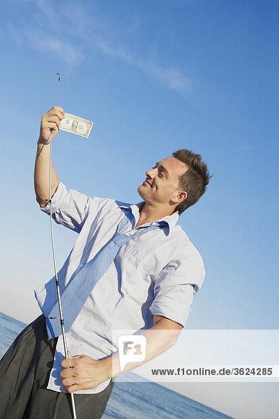 Junger Mann hält eine Angelrute und einen Dollar-Schein
