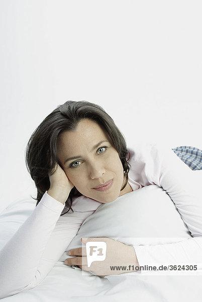 Porträt einer Frau auf dem Bett liegend