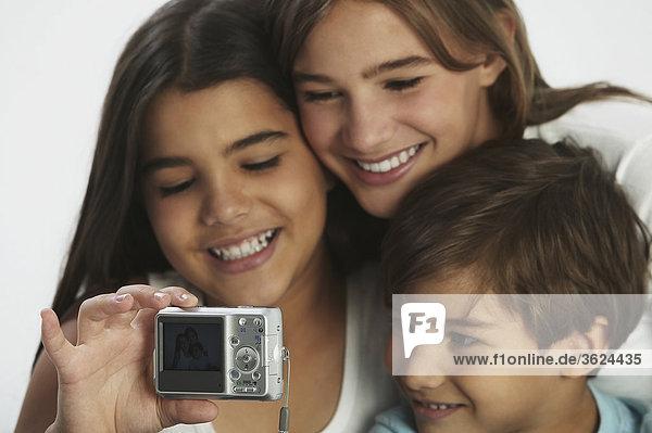 Nahaufnahme-ein Junge und seine zwei Schwestern ein Foto von sich selbst mit einer Digitalkamera