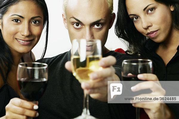 Porträt eines jungen Mannes mit zwei Frauen halten Gläser Wein