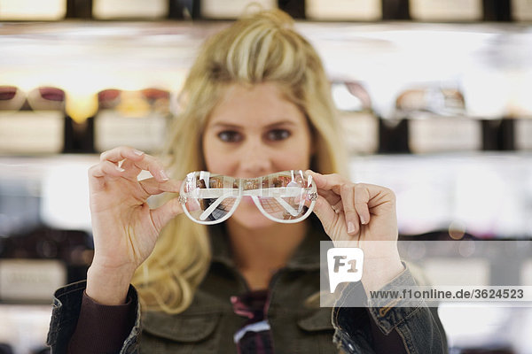 Close-up of a young woman holding sunglasses in a store
