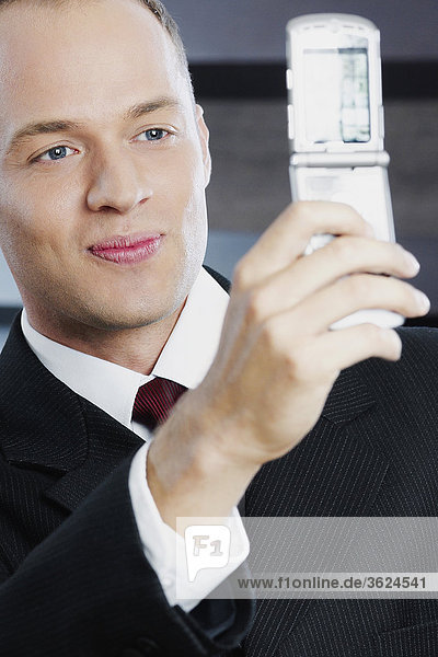 Close-up of a businessman taking his photograph with a mobile phone