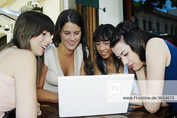 Nahaufnahme von zwei Mitte Erwachsene Frauen und zwei junge Frauen lächelnd und Blick auf einen laptop