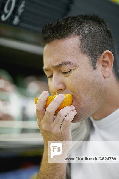 Nahaufnahme eines Mitte erwachsenen Menschen Verkostung eine orange
