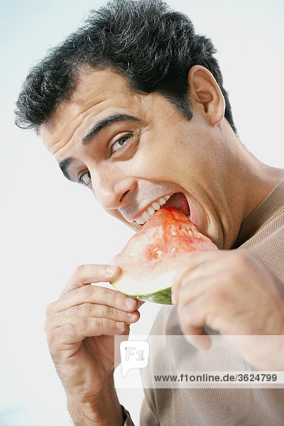 Portrait of a mid adult man eating a slice of watermelon