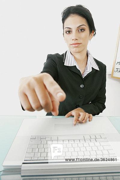 Porträt von Geschäftsfrau sitzt vor einem Laptop und nach vorne zeigen