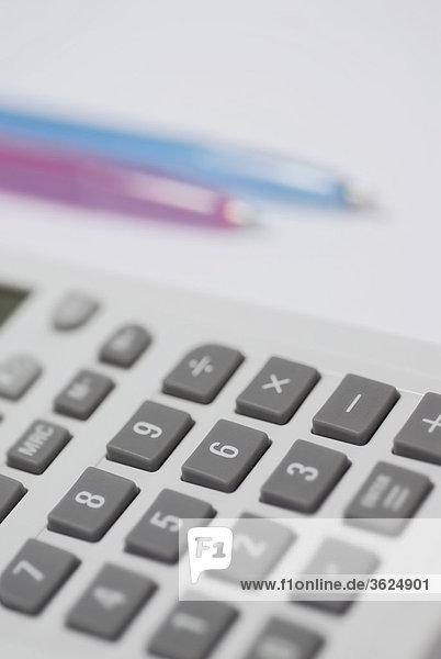 Nahaufnahme Taschenrechner mit zwei Stifte