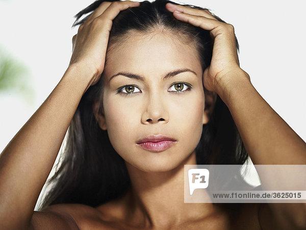 Portrait einer jungen Frau mit ihren Händen im Haar