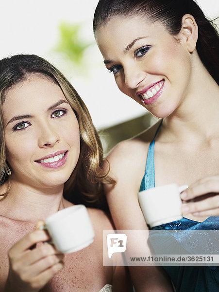 Portrait von zwei jungen Frauen halten Kaffeetassen