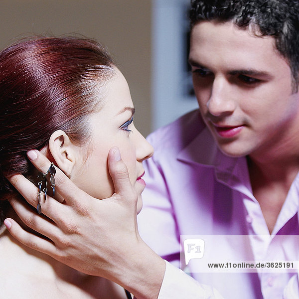 Close-up of a teenage boy holding a young woman's face