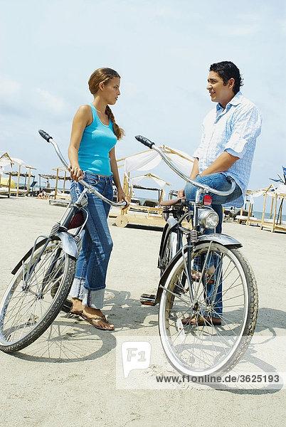 Seitenansicht ein junges paar steht am Strand mit Fahrrad