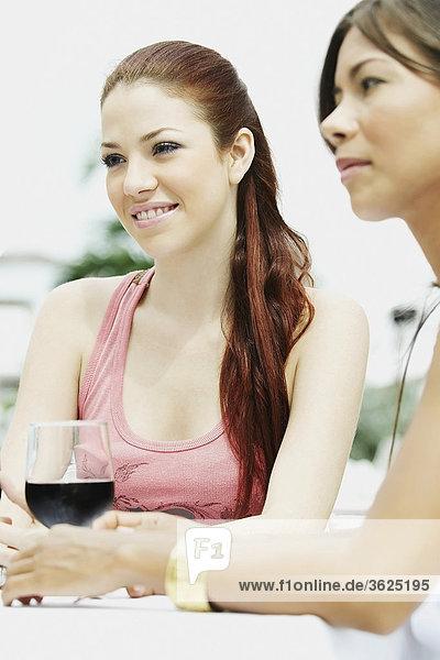 Zwei junge Frauen sitzen und halten Gläser Wein