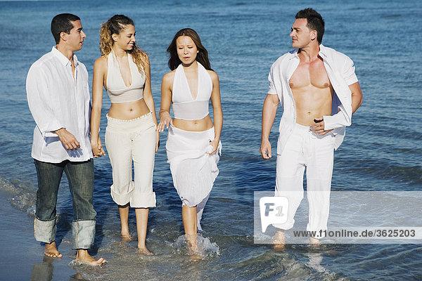 Zwei junge Frauen und ein junger Mann mit einem Mitte Erwachsenen Mann zu Fuß am Strand