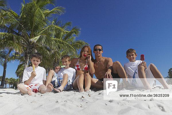 Mitte Erwachsenen Mann und ein junger Mann sitzen mit ihren Kindern am Strand