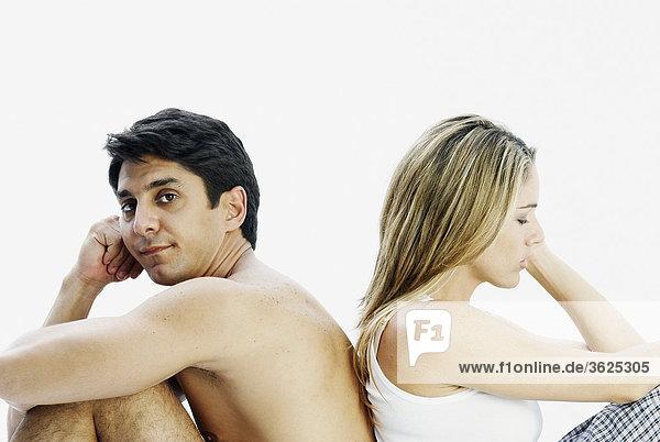 Seitenansicht ein Mitte adult paar Rücken an Rücken sitzen und ernsthafte suchen