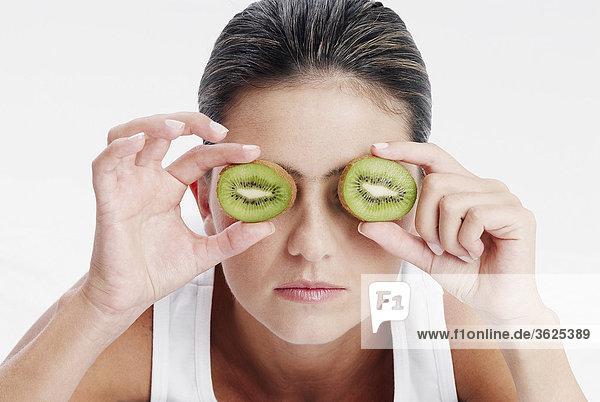 Nahaufnahme of a junge Frau hält Scheiben Kiwi Obst an ihre Augen