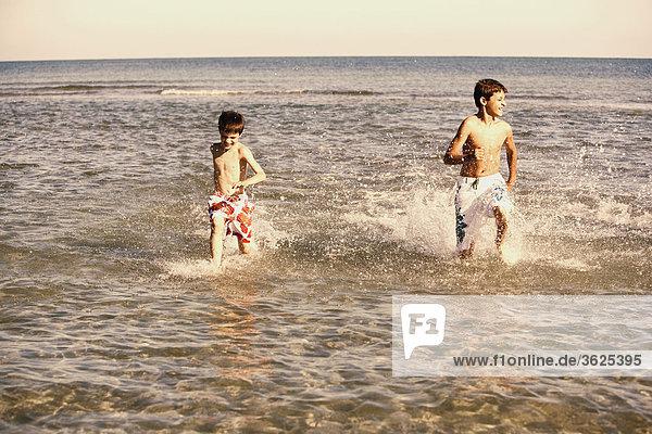 Teenager in Wasser mit seinem Bruder ausgeführt