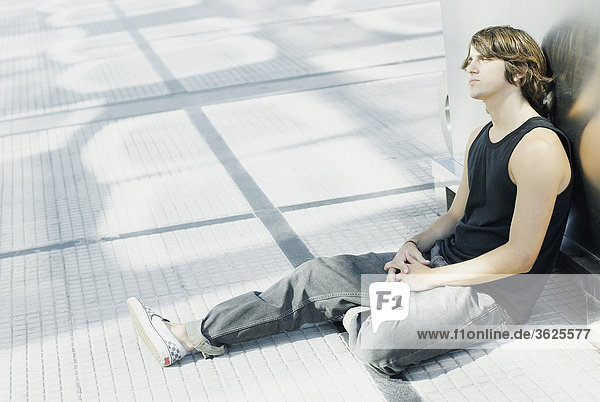 Side profile of a young man sitting on the floor