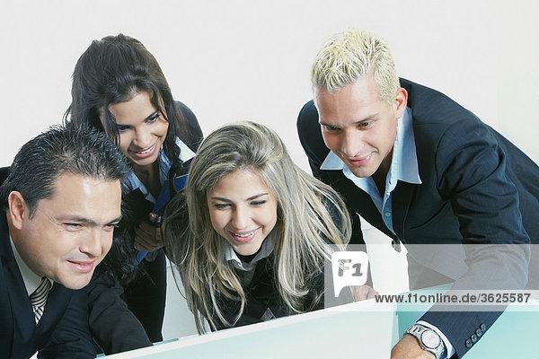 Nahaufnahme zwei Geschäftsleute und zwei Geschäftsfrauen Blick auf einem laptop